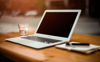 White thin laptop on wooden table
